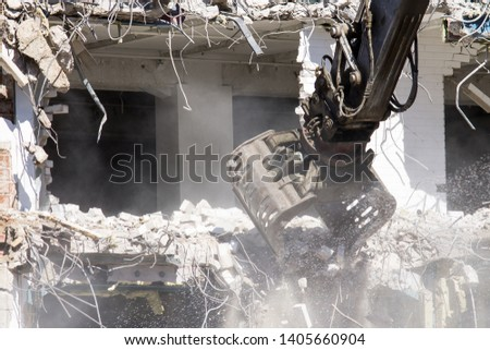 Demolition of a building in progress - Claw moving rubble, dust and water flying around