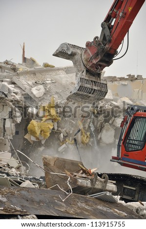 Demolition of a concrete building by an excavator to make way for new commercial development