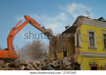 Demolition of an old house with power shovel - stock photo
