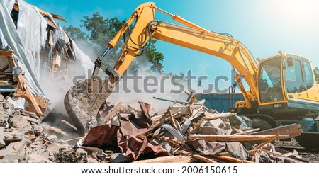 Demolition of building. Excavator breaks old house. Freeing up space for construction of new building
