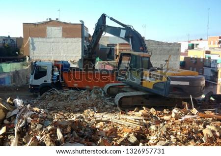 demolition team at construction site, excavator disposes demolition rubbish intro truck #1326957731