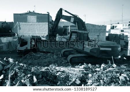 demolition team at construction site, excavator disposes demolition rubbish intro truck #1338189527