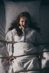 demonic obsessed yelling girl in nightgown bound with rope in bed