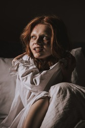 demonic smiling girl in nightgown sitting in bed