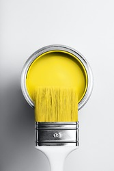 Demonstrating colors of year 2021 - Gray and Yellow. Brush with white handle on open can of yellow paint on monochrome background.