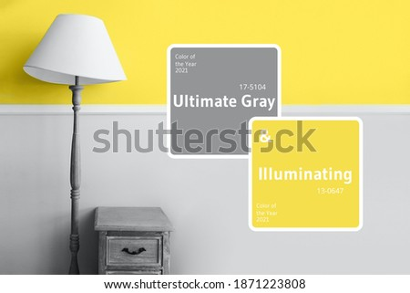 Demonstrating trendy Color of the Year 2021. Illuminating Yellow and Ultimate Gray. Duotone. Floor lamp on pastel wall background. Color Psychology. Minimalistic room interior. Depression treatment.