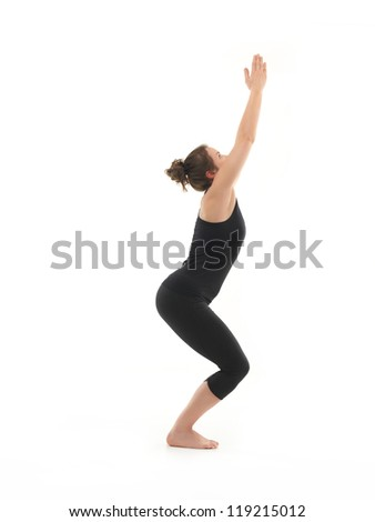 demonstration of beginner yoga posture by young woman, dressed in blac, on white background, side view