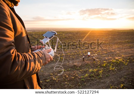 Shutterstock Demonstration of  copter. Man controls quadrocopter flight. Flying the copter over a field. Remote control in a man's hands.