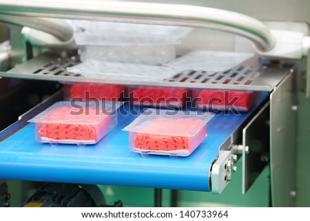 Demonstration of packaging machinery for ground meat and other meat products in plastic containers.