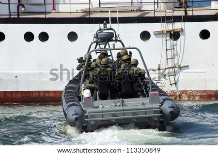 DEN HELDER, THE NETHERLANDS - JULY 7: Dutch Marines about to enter a ship during an anti piracy demonstrion at the Dutch Navy Days on July 7, 2012 in Den Helder, The Netherlands
