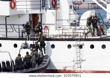 DEN HELDER, THE NETHERLANDS - JULY 7: Dutch Marines entering a ship during an anti piracy demonstrion at the Dutch Navy Days on July 7, 2012 in Den Helder, The Netherlands