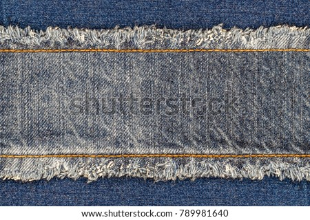 Denim blue jeans fabric frame. Bleached denim fabric with fringe edge and straight stitch with orange thread, on blue denim background, text place, copy space. Worn Jeans Casual Double Color patch