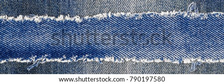 Denim frame. Ripped denim fabric with fringe edge on bleached denim background, text place, copy space. Worn Jeans Casual Double Color patch. Classic blue denim pattern texture