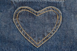 denim heart frame on denim jeans background.  denim heart patch with straight stitch with orange thread, on blue jeans background, text place, copy space.