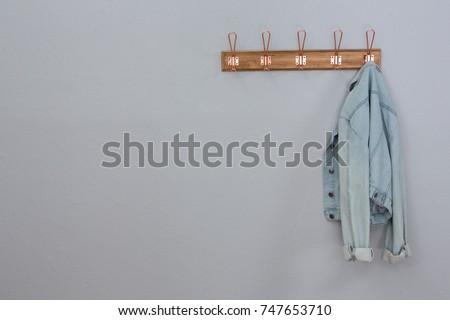 Denim jacket hanging on hook against wall