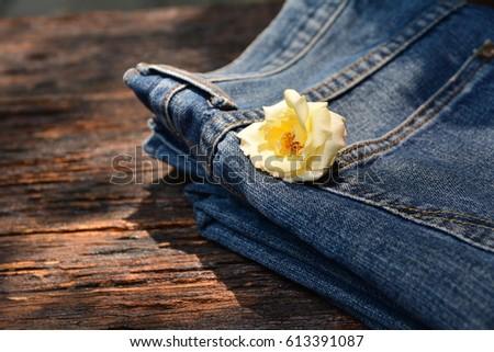 Denim jeans, Denim jeans with white flower on wooden background.