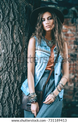 Denim style. Sexual young woman posing in jeans clothes on a street. Beauty, fashionable look.