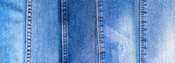 Denim texture, jeans in a line, banner background of variety of comfortable casual pants and clothes. Light blue surface of cotton fabric with orange thread seam and stitches. Copy space backdrop.