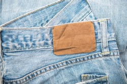 Denim texture, pile of blue jeans and blank leather label close up, variety of comfortable casual pants and clothes.