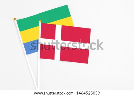 Denmark and Gabon stick flags on white background. High quality fabric, miniature national flag. Peaceful global concept.White floor for copy space. #1464525059