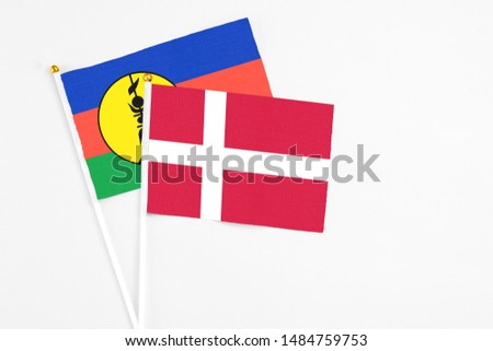Denmark and New Caledonia stick flags on white background. High quality fabric, miniature national flag. Peaceful global concept.White floor for copy space. #1484759753