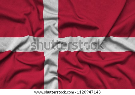 Denmark flag  is depicted on a sports cloth fabric with many folds. Sport team banner #1120947143