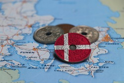 Denmark flag on the coin with heap of Danish Kroner money on the map. Concept of finance or currency or travel.