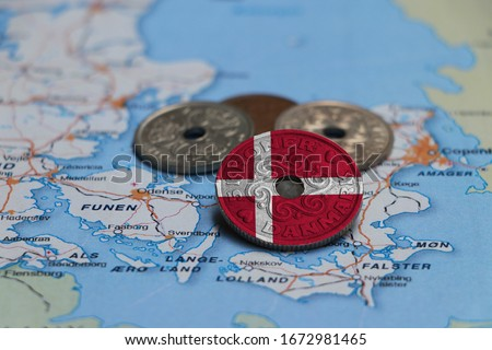 Denmark flag on the coin with heap of Danish Kroner money on the map. Concept of finance or currency or travel. Foto stock ©