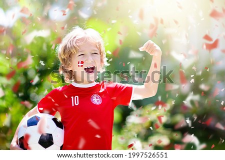 Denmark football fan cheering. Danish kids play soccer and celebrate victory on outdoor field. Danmark team supporter. Little boy in Dansk flag jersey kicking ball. Sports training for children. Сток-фото ©