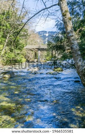 Denny Creek with rocks on the shore flows under a bridge. Zdjęcia stock ©