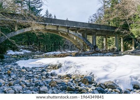 Denny Creek with snow  on the shore flows under a bridge. Zdjęcia stock ©