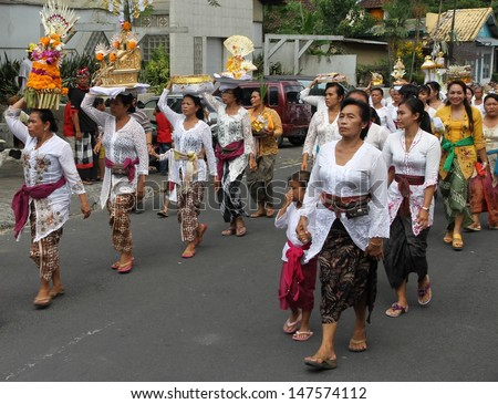DENPASAR, BALI - MAY 12: A street procession of local village women with offerings on their heads for a Ngaben or cremation ceremony in Ubud, Bali, Denpasar, Indonesia on May 12, 2013.