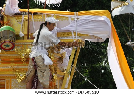 DENPASAR, INDONESIA - MAY 12: A Balinese holy man rides the funeral pyre scaring away evil spirits in a Ngaben or cremation ceremony in Ubud, Denpasar, Bali, Indonesia on May 12, 2013.