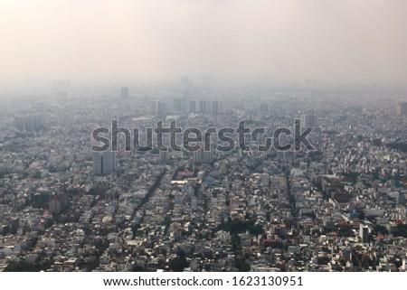 Dense air pollution and smog over Saigon, Vietnam (Ho chi Minh City). Overpopulated city, metropolis, urban sprawl. Aerial view.