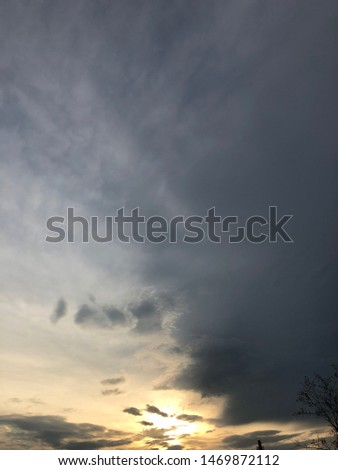 Dense clouds in twilight sky in evening.Image of cloud sky on evening time.Evening sky scene with golden light from the setting sun. Tree silhouette on a cloudy evening sky #1469872112
