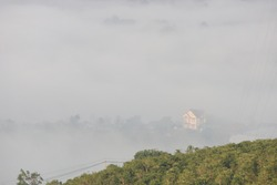 dense fog cover church and small village at the foot of hill with green coffee farm background
