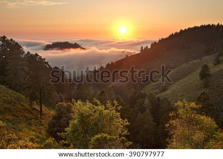 Dense fog rolls in over the Pacific Ocean at sunset over coastal California mountains