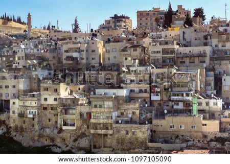 densely packed and poor neighborhood, with apartment houses and a mosque, built on a hillside in downtown Jerusalem, Israel, as seen from the Old City