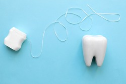 Dental care concept. Teeth model with dental floss on blue background.