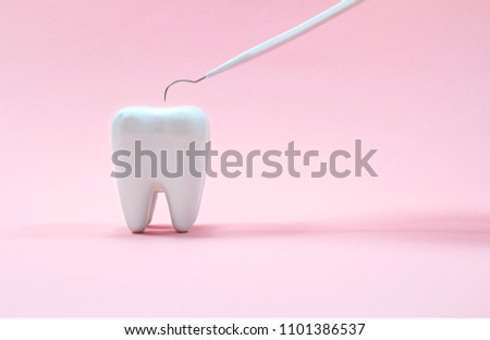 Dental explorer probe with healthy tooth model on pink background.