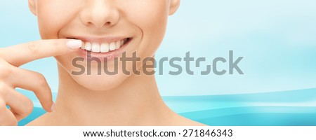 dental health, beauty, hygiene and people concept - close up of smiling woman face pointing to teeth over blue wavy background