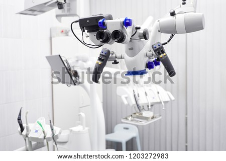 Dental microscope. on the background of modern dentistry. Medical equipment. operating microscope. with rotary double binocular.dental microscope.white cabinet working room.purple.