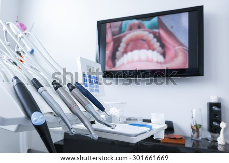 Dental office - specialist tools, drills, handpieces and laser with live picture of teeth in the background. Dental care, dental hygiene, checkup and therapy concept.