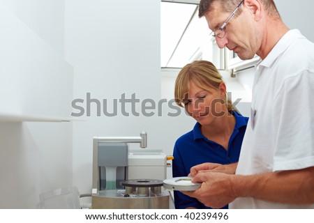 Dental technician explaining a pin drill unit