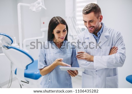 dentist and assistant looking at digital tablet screen in modern dental clinic