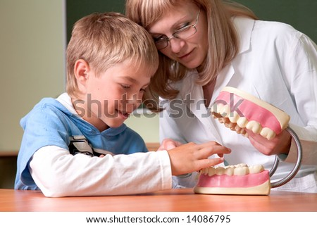 Dentist and boy with jaw of dentist's sample teeth