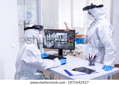 Dentist and nurse discussing patient teeth issues dressed in ppe suit. Medical specialist wearing protective gear against coronavirus during global outbreak looking at radiography in dental office. Foto stock ©