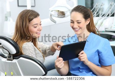 Dentist and patient choosing treatment in a consultation with medical equipment in the background