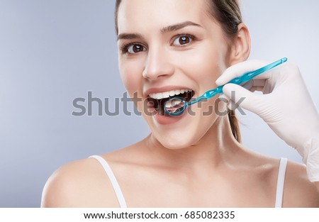 Dentist and patient, teethcare. Healthcare, stomatological concept for dentists. Smiling girl with snow-white teeth with special stomatological equipment in her mouth