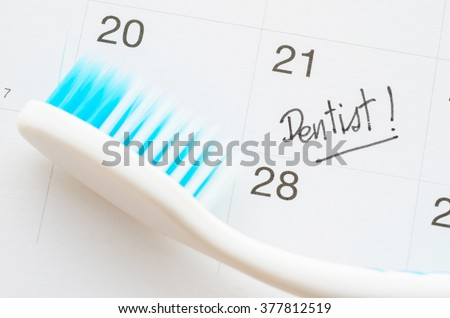 Dentist appointment date on calendar with toothbrush.